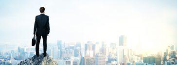 都会の見える頂上に立つビジネスマン