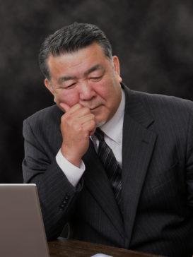 PCの前で考え込む老ビジネスマン